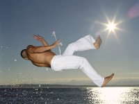 Young man performing capoeira on beach at dusk